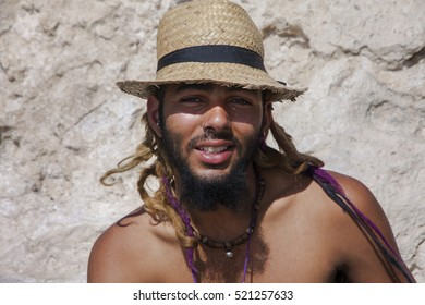 Young bearded man wearing a straw hat and golden and purple dread locks