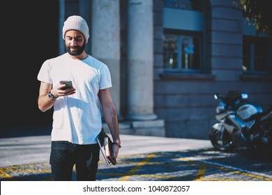 Young bearded positive entrepreneur dressed in stylish clothes watching interesting video in website on smartphone connected to 4G.Handsome hipster guy booking online while strolling outdoors