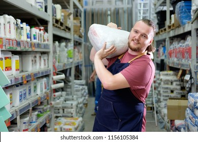 Young bearded salesman carries a pack of plaster on his shoulder in counstruction store