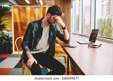 Young bearded skilled male IT developer dressed in stylish outfit deeply thinking about new feature implementation for startup.Smart tired hipster guy planning working schedule sitting in office