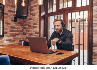 Young bearded specialist with earphones talking to employer through video call during online interview