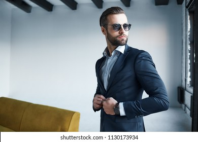 Young bearded stylish businessman leader indoors at office wearing sunglasses with watch looking aside serious