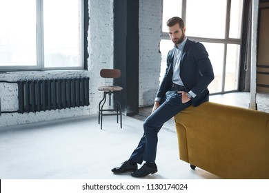 Young bearded stylish businessman leader indoors at office looking aside serious