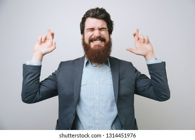 Young bearded successful businessman praying with crossed fingers over gray background