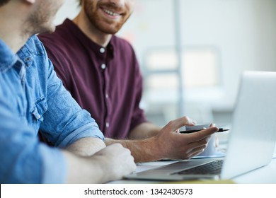 Young bearded webdesigner in casualwear pointing at laptop display while discussing online data with colleague