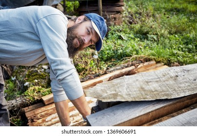 Young bearded worker handles timber struts. Portrait of a handsome man with blue eyes and hipster beard looking at camera.