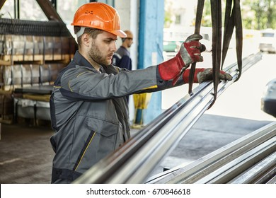 Young bearded worker in a hardhat and protective uniform working at the metal factory copyspace profession occupation engineer builder manufacturing operating concept
