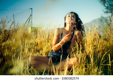 Young beatiful girl in denim shirts resting in the field on a sunny day and enjoying nature.