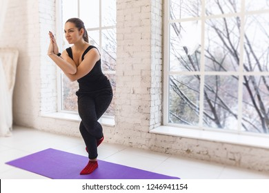 Young beaute sporty yoga girl in eagle position with hands together