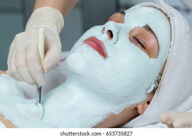 A young beautician is gently applying a face mask on the client's face and her neck. She looks very calm.
