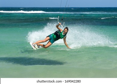young beautifil girl - kiter riding in the clear waves of the Indian Ocean on the island of Mauritius. Kiting on a background of waves in the spray of ocean