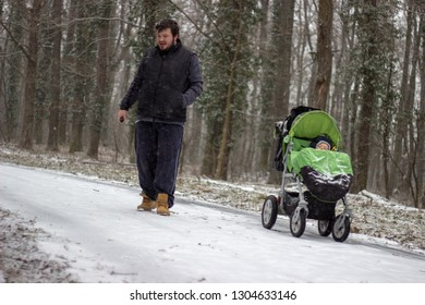young beautiful adorable father holding the ecigarette looks like walking away from his cute beautiful adorable son sitting and sleeping in the green stroller in the forest footpath covered with snow