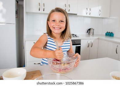 young beautiful and adorable girl 6 or 7 years old cooking and baking at home kitchen preparing strawberry cake with bowl smiling happy and confident in nutrition and children education concept