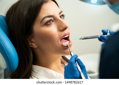 Young beautiful young adult woman getting dental anesthesia, closeup shot
