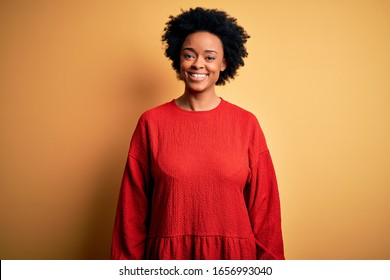 Young beautiful African American afro woman with curly hair wearing casual sweater with a happy and cool smile on face. Lucky person.