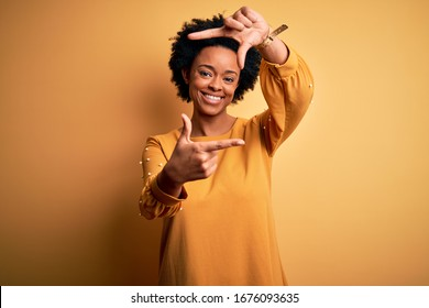 Young beautiful African American afro woman with curly hair wearing casual t-shirt smiling making frame with hands and fingers with happy face. Creativity and photography concept.