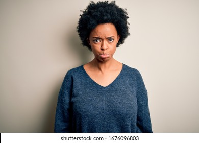 Young beautiful African American afro woman with curly hair wearing casual sweater depressed and worry for distress, crying angry and afraid. Sad expression.