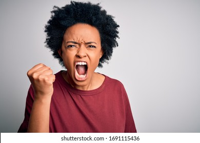 Young beautiful African American afro woman with curly hair wearing casual t-shirt standing angry and mad raising fist frustrated and furious while shouting with anger. Rage and aggressive concept.