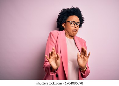 Young beautiful African American afro businesswoman with curly hair wearing pink jacket disgusted expression, displeased and fearful doing disgust face because aversion reaction.