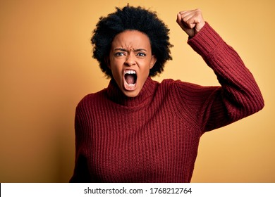 Young beautiful African American afro woman with curly hair wearing casual turtleneck sweater angry and mad raising fist frustrated and furious while shouting with anger. Rage and aggressive concept.