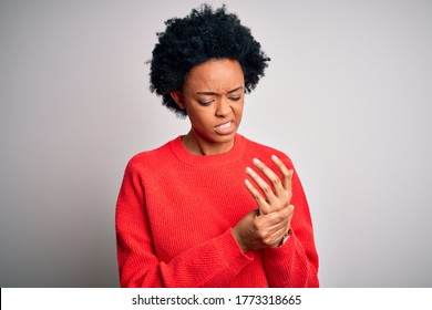 Young beautiful African American afro woman with curly hair wearing red casual sweater Suffering pain on hands and fingers, arthritis inflammation