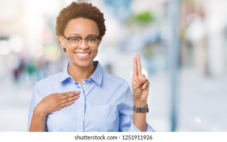 Young beautiful african american business woman over isolated background Swearing with hand on chest and fingers, making a loyalty promise oath
