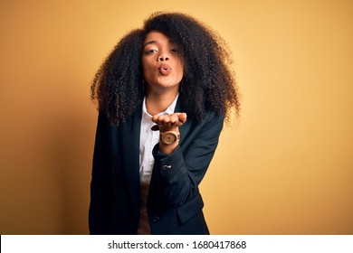 Young beautiful african american business woman with afro hair wearing elegant jacket looking at the camera blowing a kiss with hand on air being lovely and sexy. Love expression.