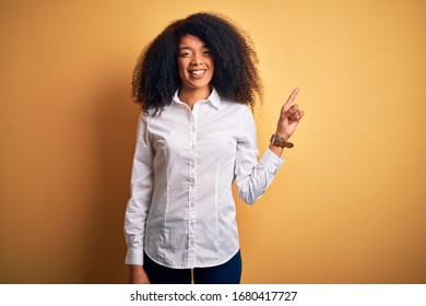 Young beautiful african american elegant woman with afro hair standing over yellow background with a big smile on face, pointing with hand finger to the side looking at the camera.