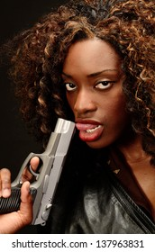 A young beautiful african american female holds a semi automatic pistol during this dark photo shoot against black