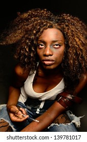 A young beautiful african american female poses as a track whore shooting up narcotics in this dark photo shoot against black