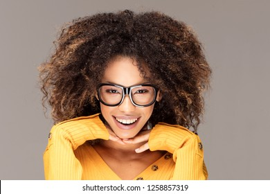Young beautiful african american girl with an afro hairstyle. Laughing girl wearing eyeglasses. Portrait.