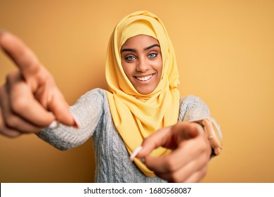 Young beautiful african american girl wearing muslim hijab over isolated yellow background pointing to you and the camera with fingers, smiling positive and cheerful