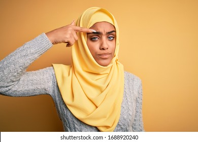 Young beautiful african american girl wearing muslim hijab over isolated yellow background pointing unhappy to pimple on forehead, ugly infection of blackhead. Acne and skin problem