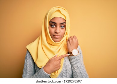 Young beautiful african american girl wearing muslim hijab over isolated yellow background In hurry pointing to watch time, impatience, looking at the camera with relaxed expression