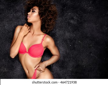 Young beautiful african american girl posing in red sensual lingerie over dark background. Girl with afro and glamour makeup. Studio shot. Fit body.