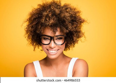 a640d5ab50 Young beautiful african american girl with an afro hairstyle. Laughing girl  wearing eyeglasses. Portrait