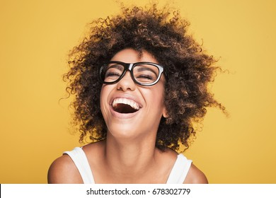 Young beautiful african american girl with an afro hairstyle. Attractive girl wearing eyeglasses. Portrait. Yellow background.