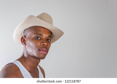 A young beautiful african american man shot in studio with yellow cowboy hat