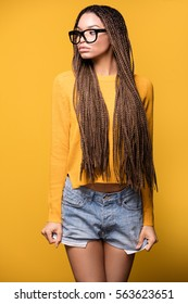 Young beautiful african american teenager girl with long braids hairstyle and fashionable eyeglasses. Yellow background.
