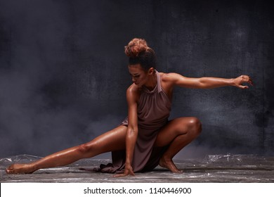 Young beautiful african american woman dancing in the water.