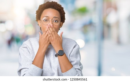 Young beautiful african american woman wearing glasses over isolated background shocked covering mouth with hands for mistake. Secret concept.