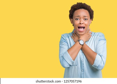 Young beautiful african american woman over isolated background shouting and suffocate because painful strangle. Health problem. Asphyxiate and suicide concept.