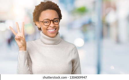 Young beautiful african american woman wearing glasses over isolated background showing and pointing up with fingers number three while smiling confident and happy.
