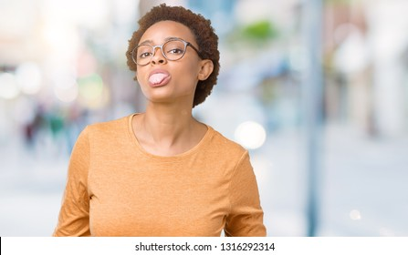 Young beautiful african american woman wearing glasses over isolated background sticking tongue out happy with funny expression. Emotion concept.