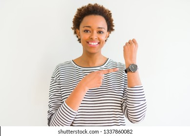 Young beautiful african american woman wearing stripes sweater over white background In hurry pointing to watch time, impatience, upset and angry for deadline delay