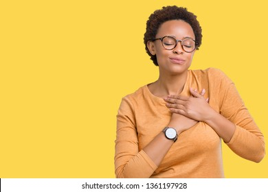 Young beautiful african american woman wearing glasses over isolated background smiling with hands on chest with closed eyes and grateful gesture on face. Health concept.