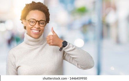 Young beautiful african american woman wearing glasses over isolated background doing happy thumbs up gesture with hand. Approving expression looking at the camera showing success.
