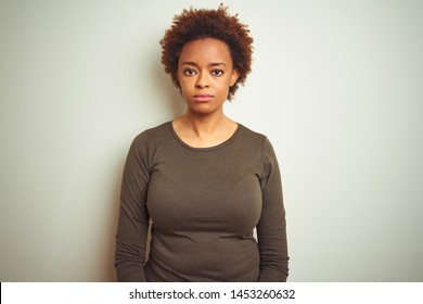 Young beautiful african american woman with afro hair over isolated background with serious expression on face. Simple and natural looking at the camera.
