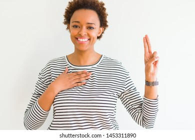 Young beautiful african american woman wearing stripes sweater over white background Swearing with hand on chest and fingers, making a loyalty promise oath