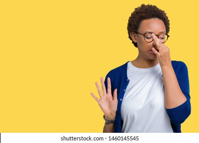 Young beautiful african american woman wearing glasses over isolated background smelling something stinky and disgusting, intolerable smell, holding breath with fingers on nose. Bad smells concept.